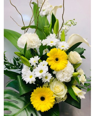 Basket of yellow, white and green flowers